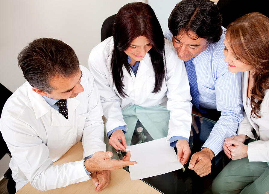 Business people negotiating medical insurance with a group of doctors