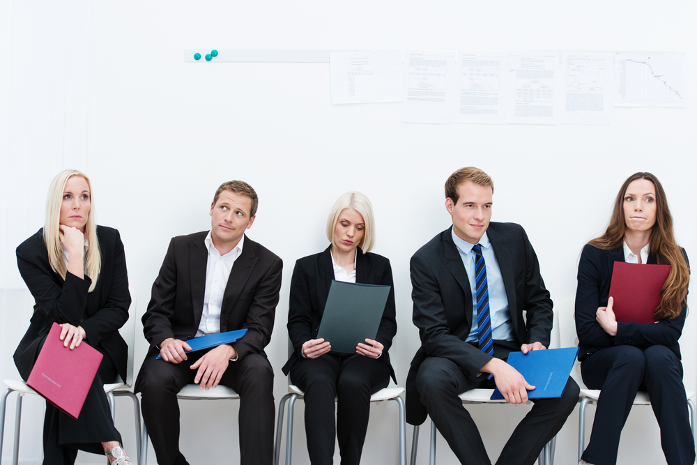 Group of applicants for a vacant post or corporate job sitting in a long line with folders containing their credentials carefully ignoring each other-1